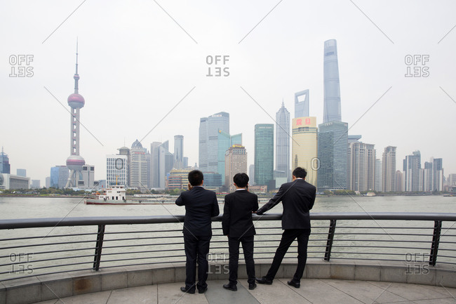 Shanghai, China - March 30, 2016: Young businessmen talking on their smartphones at the Bund in Shanghai, China
