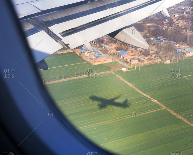 An airplane casting a shadow on a field as it approaches Shanghai Pudong International Airport in Shanghai, China