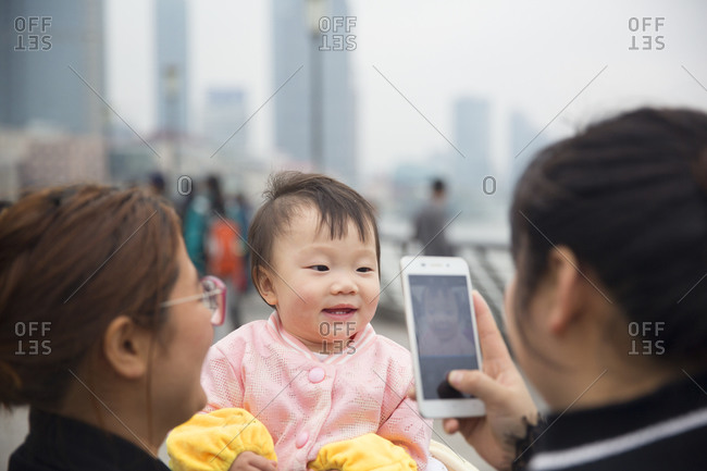 Shanghai, China - April 2, 2016: Mother photographing her baby with a smartphone in Shanghai, China