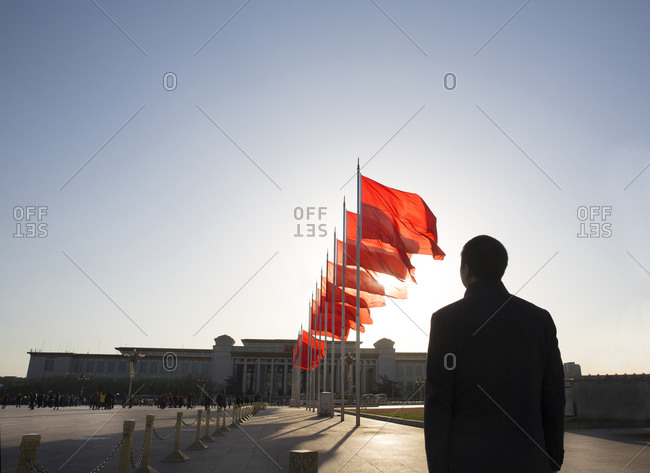 Beijing, China - March 22, 2016: Silhouette of a man standing beneath a row of red flags in Tiananmen Square, Beijing, China