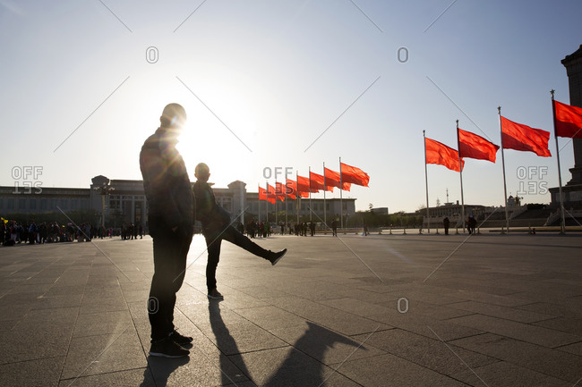 Beijing, China - March 22, 2016: Silhouette of men standing beside a row of red flags in Tiananmen Square, Beijing, China