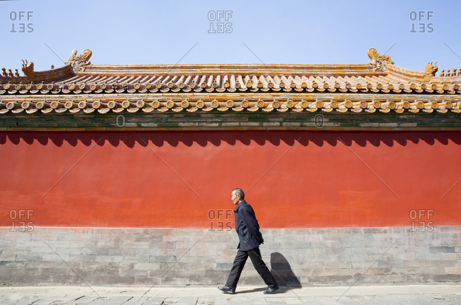 Beijing, China - March 22, 2016: Chinese man walking through the Forbidden City in Beijing, China