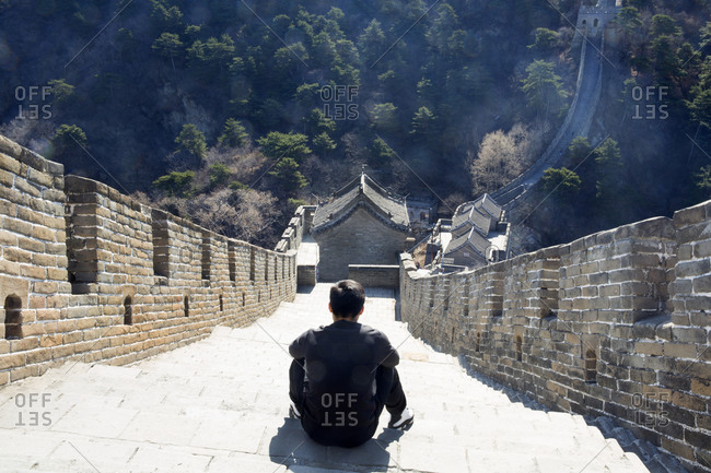 Man sitting near the Mutianyu section of the Great Wall of China northeast of central Beijing, China