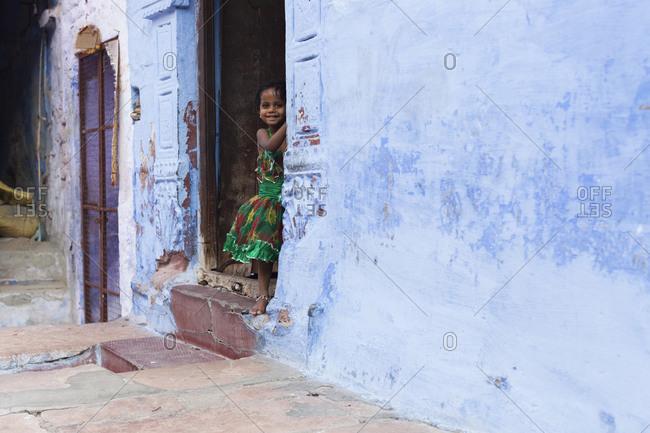 April 14, 2016: Little girl standing in the doorway, India