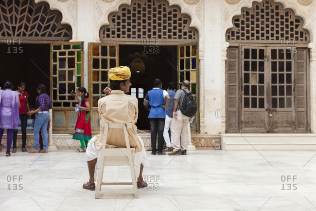 April 14, 2016: Man sitting in chair in front of building in India