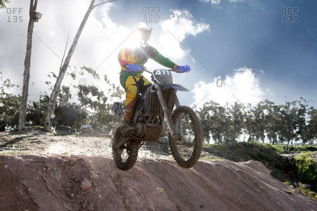 Young male motocross racer jumping mid air down mud hill