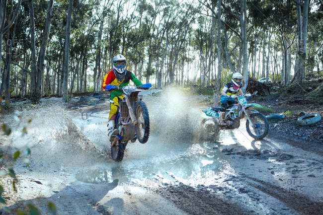 Two young male motocross riders racing on dusty track