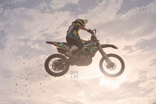 Silhouetted young male motocross racer jumping mid air