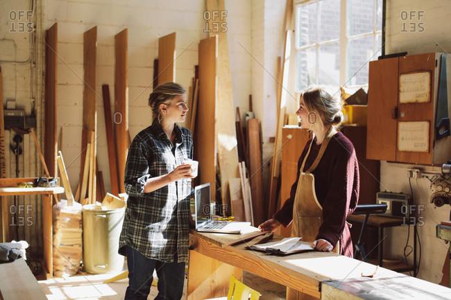 Two craftswomen drinking coffee in pipe organ workshop
