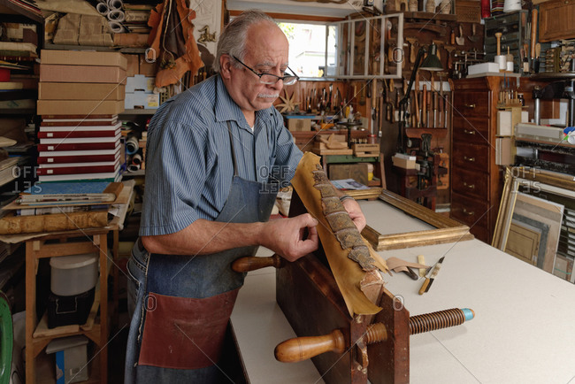 Senior man repairing fragile antique book spine in traditional bookbinding workshop