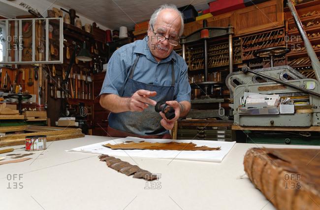 Senior man repairing fragile book spine in traditional bookbinding workshop