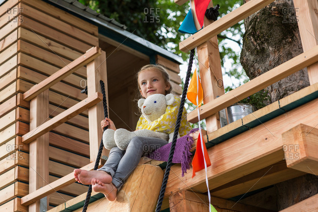 Girl with soft toy in tree house