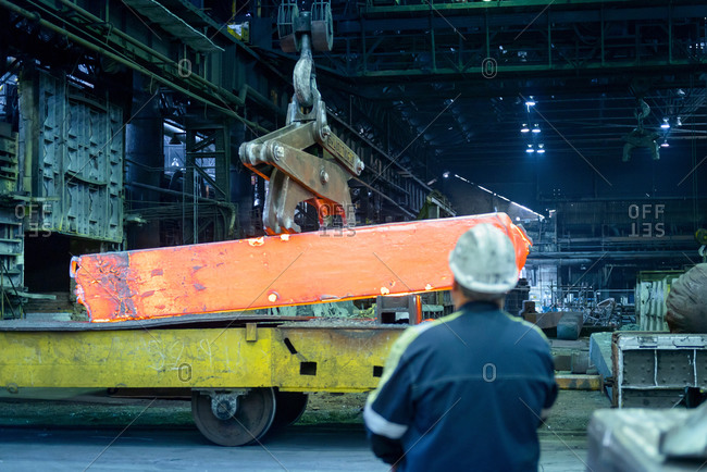 Crane operator with red hot steel in furnace of steelworks
