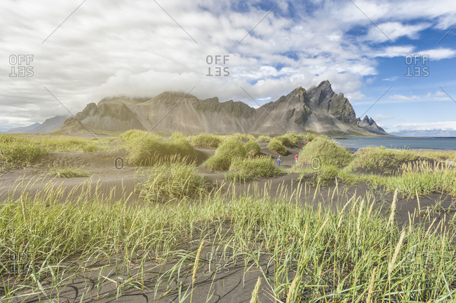 Distant view of brother and sister playing in sand dune, Stokksnes, Iceland