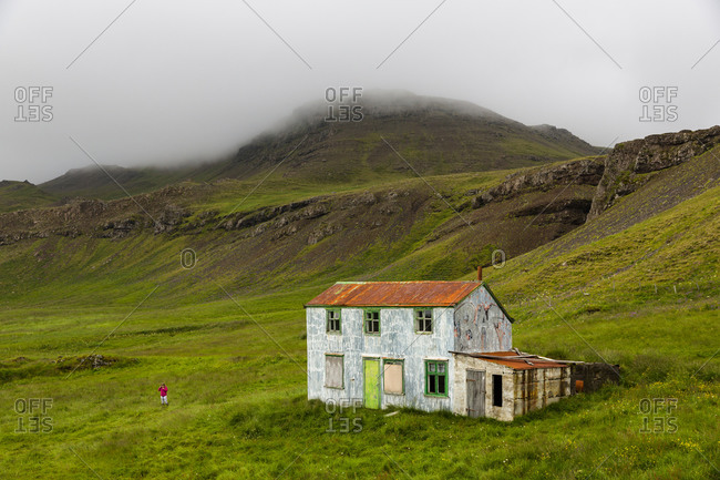 Distant view of girl playing near abandoned house, Stryta, Iceland
