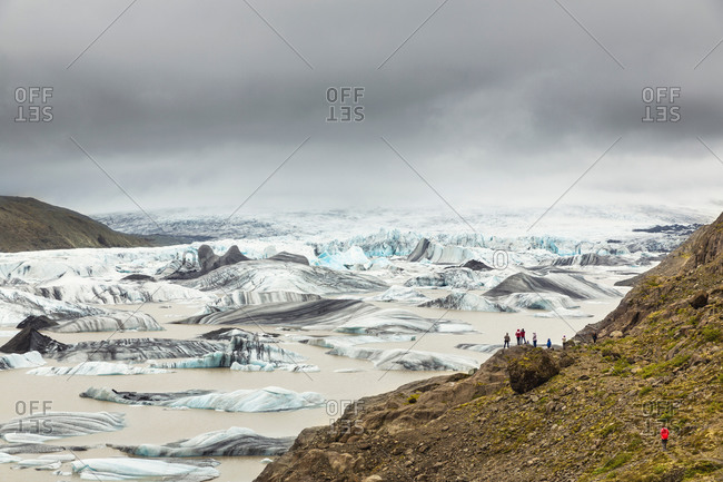 Distant view of tourists gazing at Hoffellsjokul glacier, Hornafjordur, Iceland,