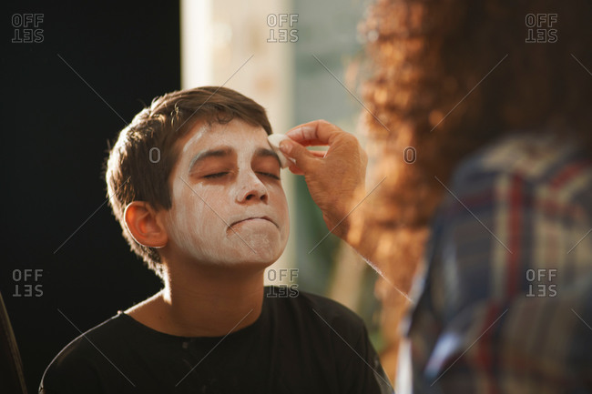 Mother painting sons face white for Halloween