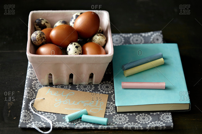 Quail and chicken eggs, chalk, notebook, kitchen towel