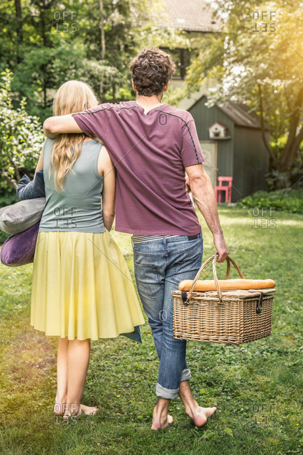 Couple carrying cushions and picnic basket in garden