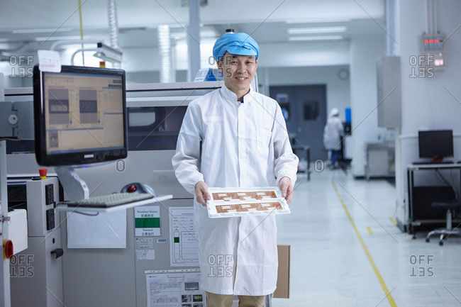 Portrait of worker in factory showing functional circuits on flexible surfaces
