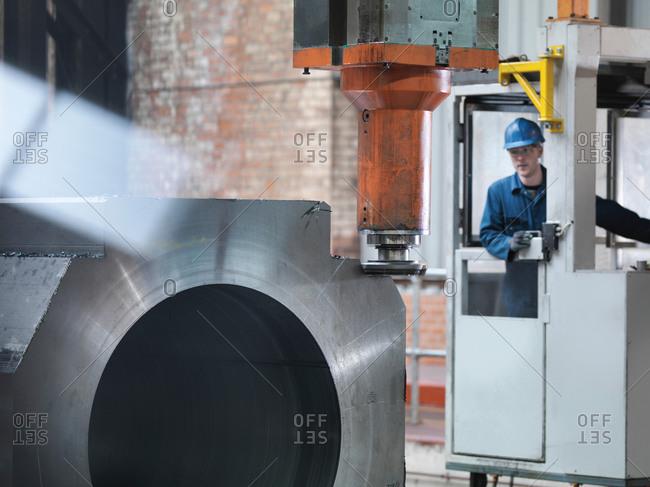 Worker cutting steel on gantry milling machine in engineering factory