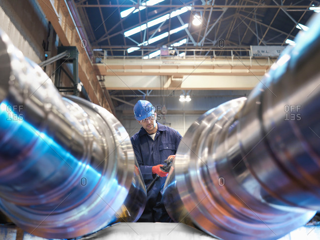 Hardness testing of steel part in engineering factory, low angle view