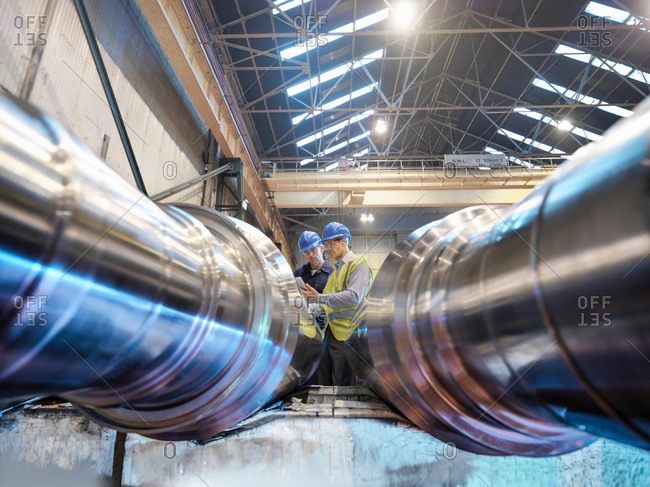 Engineers inspecting finished steel rollers in engineering factory, low angle view