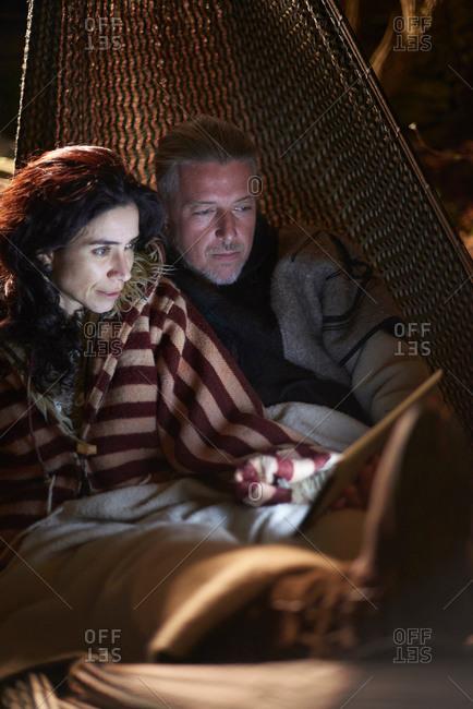 Mature hippy couple in garden hammock at night looking at digital tablet