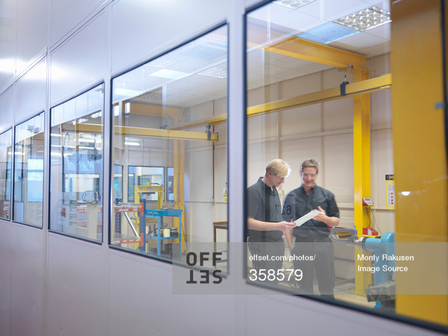 Engineers in discussion in factory offices