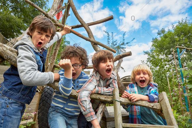 Four boy shouting on homemade climbing frame in garden