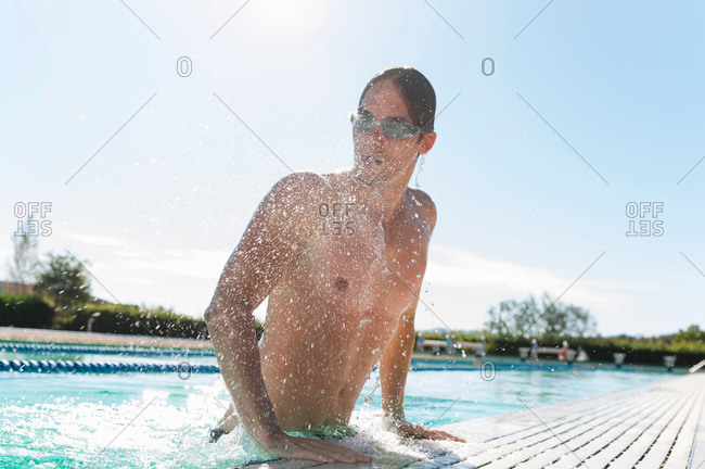 Mid adult man getting out of swimming pool, Sardinia, Italy