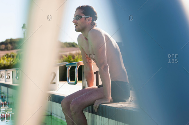 Mid adult male swimmer sitting on side of swimming pool, Sardinia, Italy