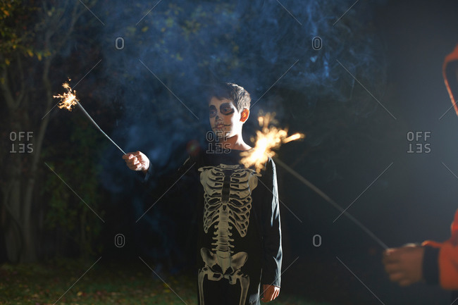 Boy wearing Halloween skeleton costume with sparkler in garden at night