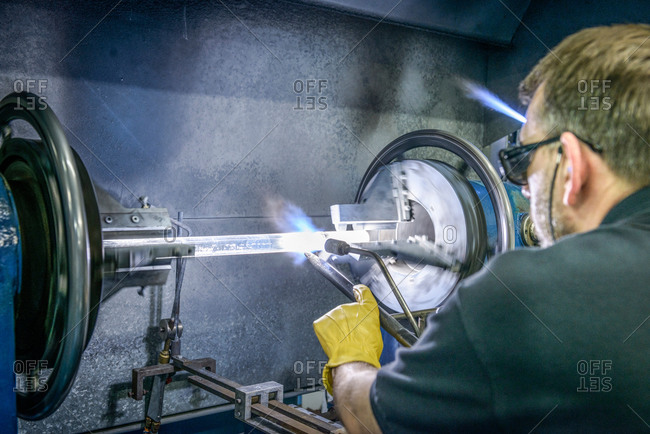 Industrial glass blower forming a tube on lathe