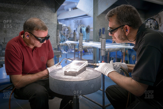 Two industrial glass blowers constructing intricate glass part