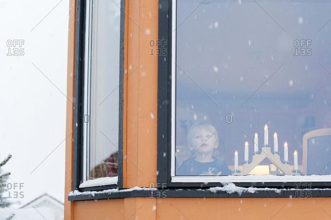 Boy waiting behind window