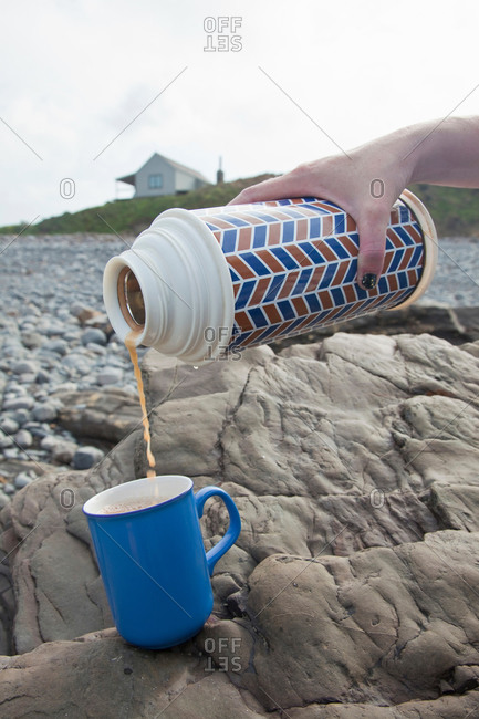 Female hand pouring tea from drinks flask on Millook Beach, Cornwall, UK