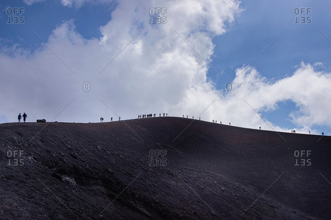 Distant view of silhouetted tourists on top of Mount Etna, Catania, Sicily, Italy