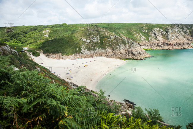 View of vacationers on beach, Porthcurno, Cornwall, UK