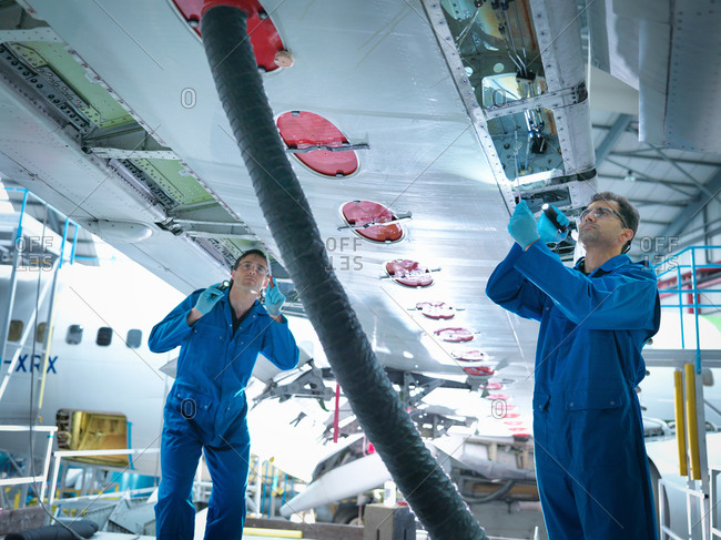 Engineers working on aircraft wing