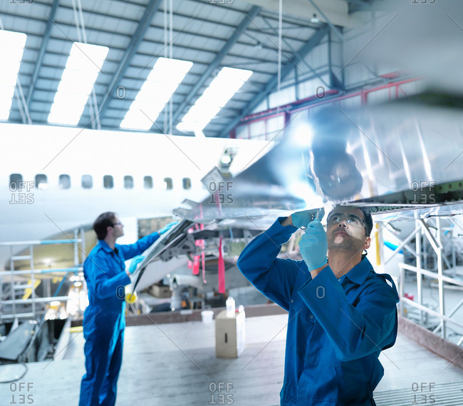 Engineers working on wing in aircraft maintenance factory