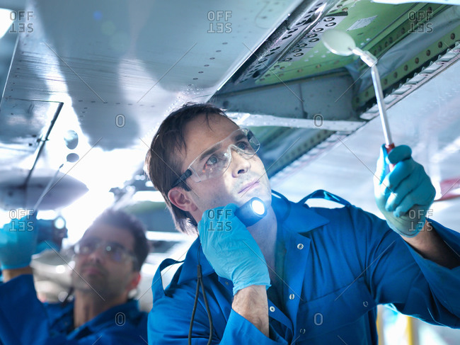 Engineers working on aircraft wing in aircraft maintenance factory, close up