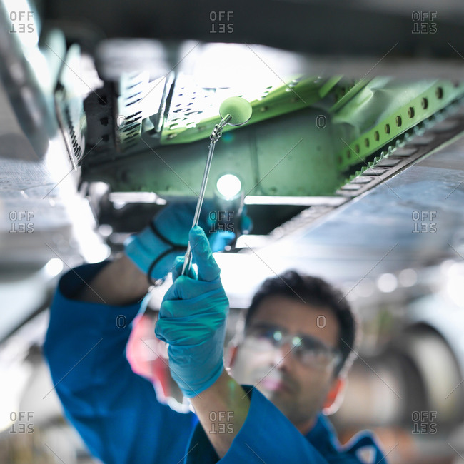 Close up of an engineer working on aircraft wing in aircraft maintenance factory