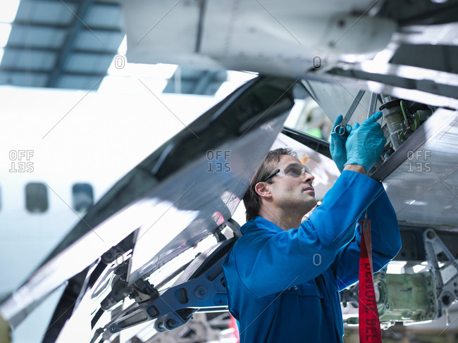 Engineer working on aircraft wing in aircraft maintenance factory, close up