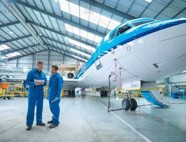 Engineers in discussion by aircraft in aircraft maintenance factory
