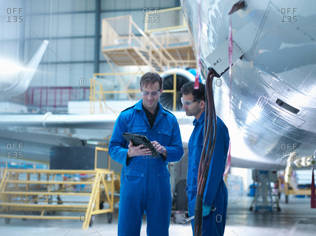 Engineers using digital tablet and in discussion in aircraft maintenance factory