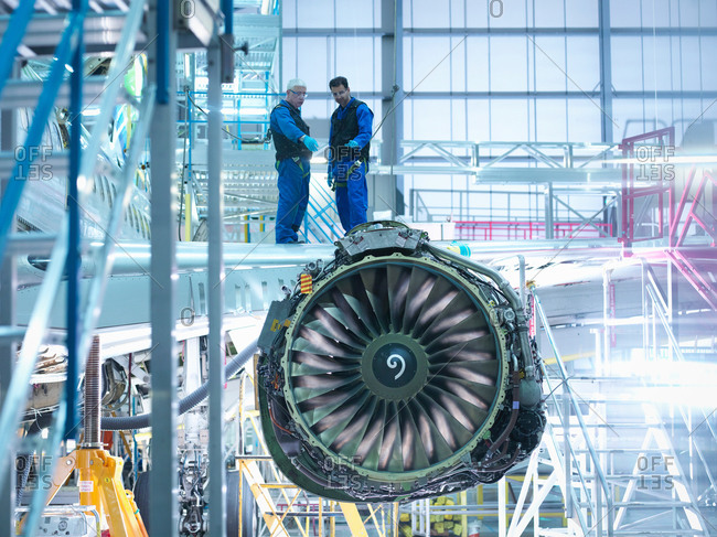Aircraft engineers standing on wing with jet engine in aircraft maintenance factory