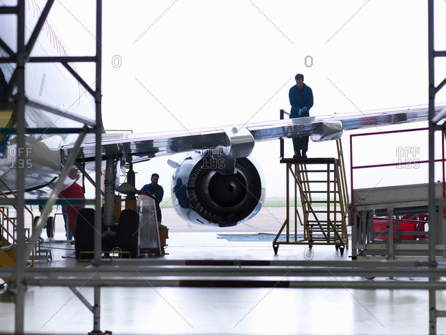 Engineer on ladder working on aircraft wing in aircraft maintenance factory