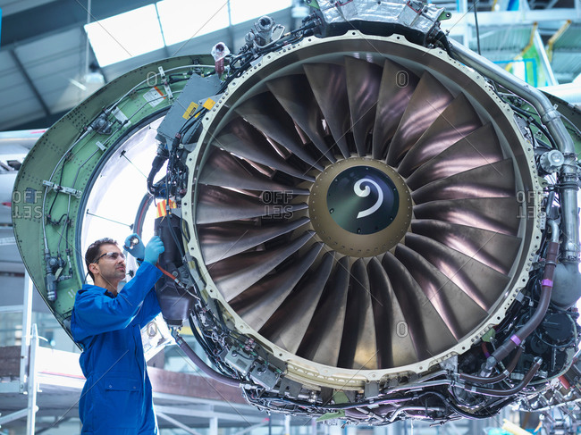 Engineers working on aircraft engine in aircraft maintenance factory