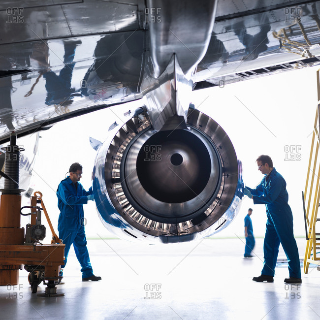 Engineers working on aircraft engine and wing in aircraft maintenance factory